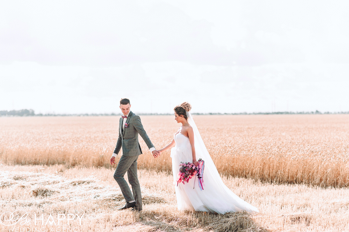 Жених ведет невесту за руку на фоне поля