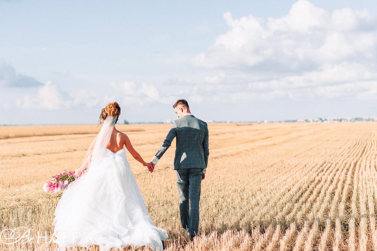 Жених и невеста идут по полю держась за руки