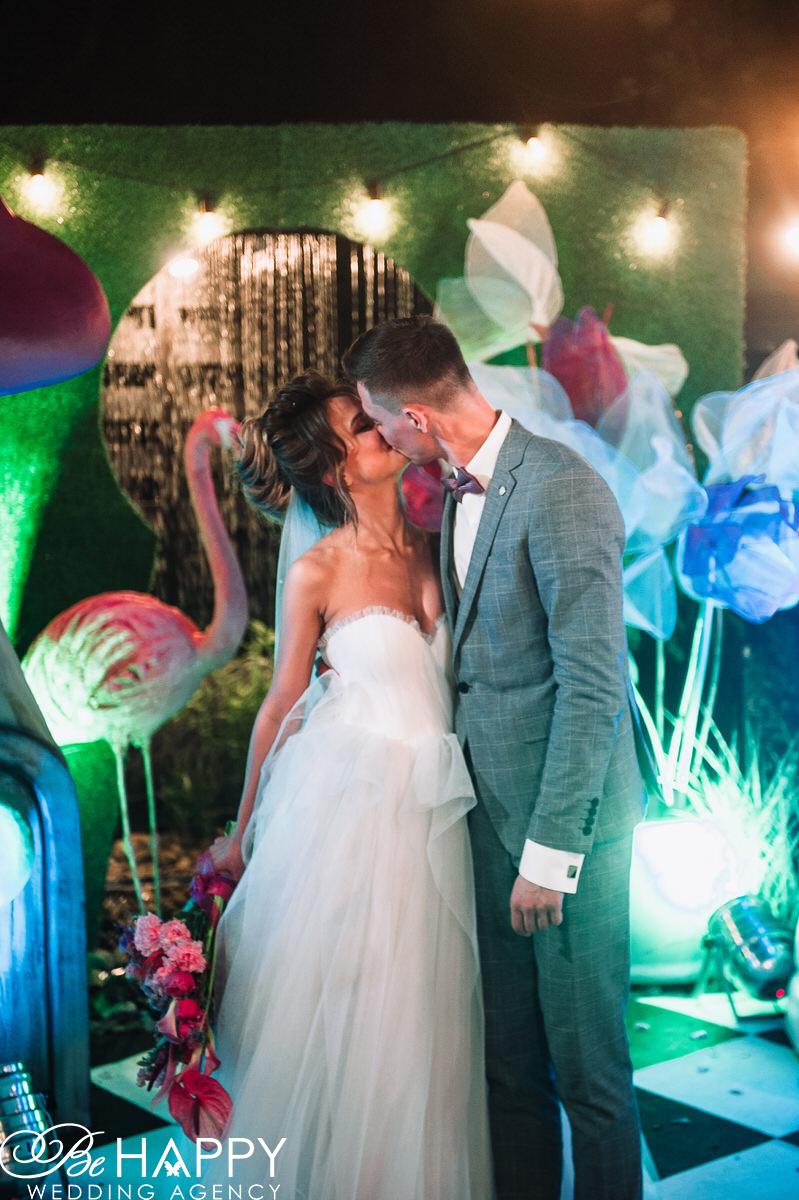 Фото целующихся молодоженов в свадебной фото-зоне