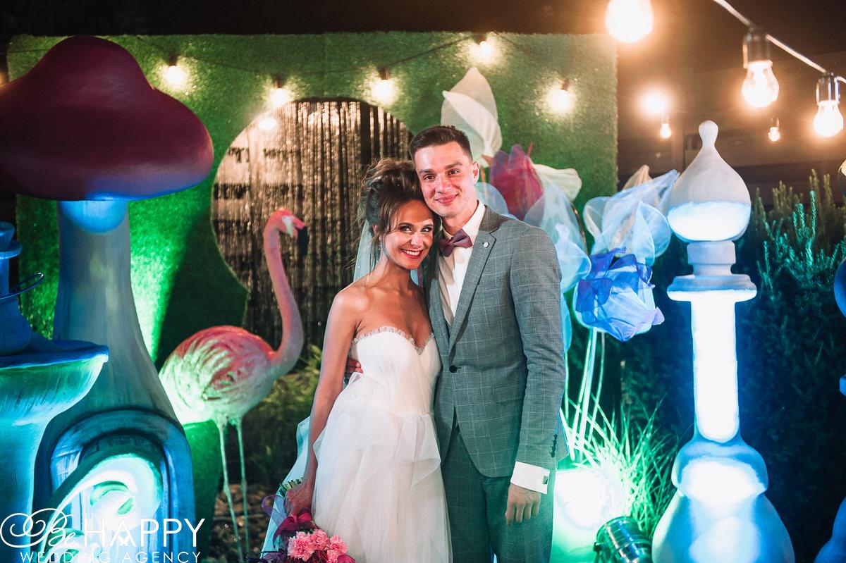 Счастливые молодожены на фоне свадебных декораций