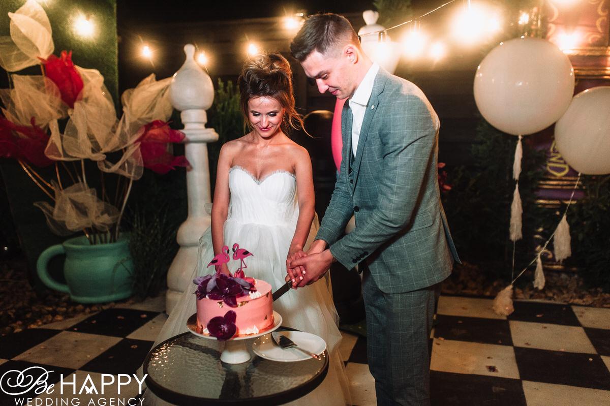 Жених и невеста разрезают свадебный торт