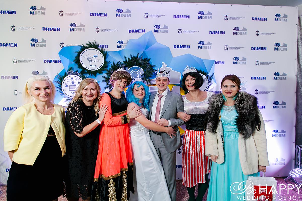 Групповое фото гостей корпоративного мероприятие на фоне логотипа MDEM