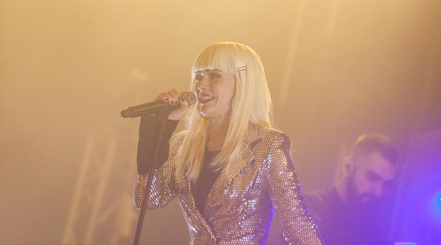 Юлия Санина в блестящем пиджаке на сцене