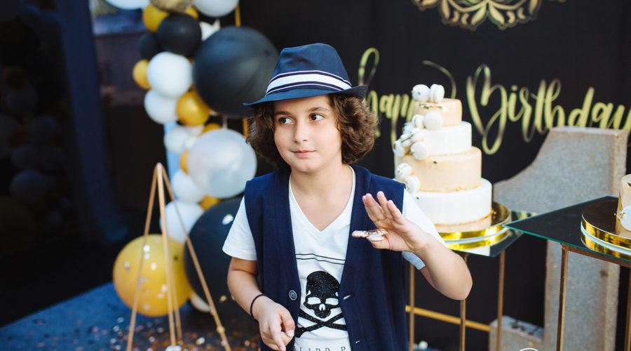 Фото мальчика в шляпе на фоне праздничных тортов