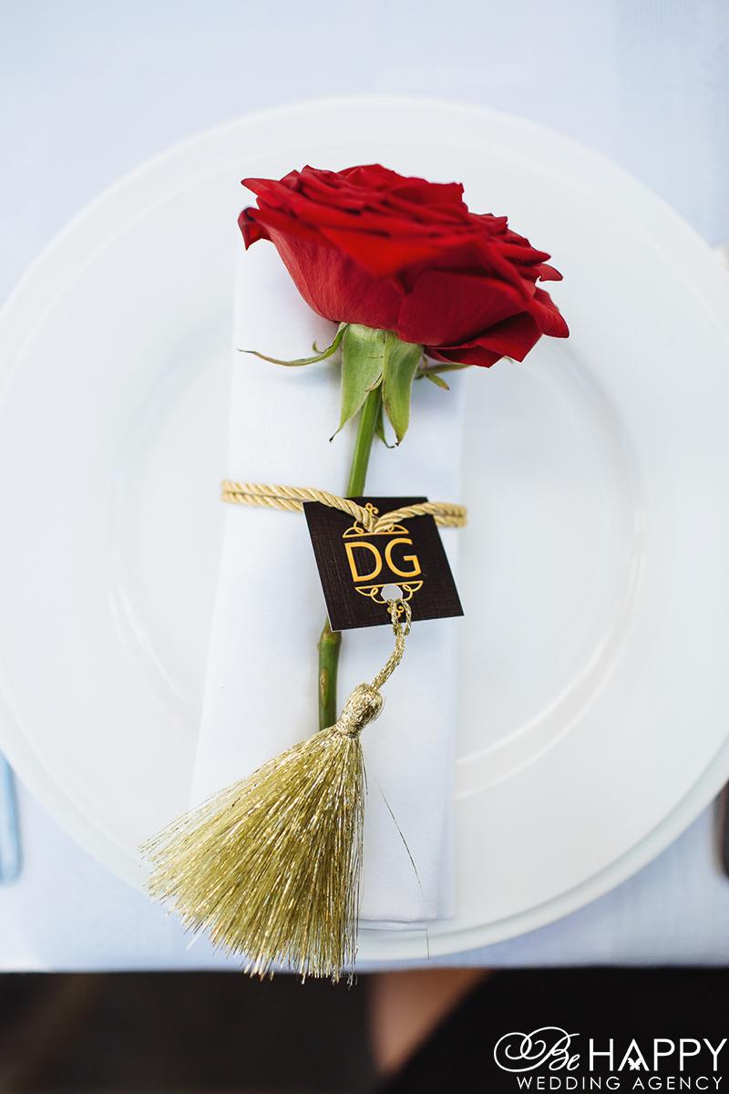 Фото красной розы с золотой кисточкой на тарелке