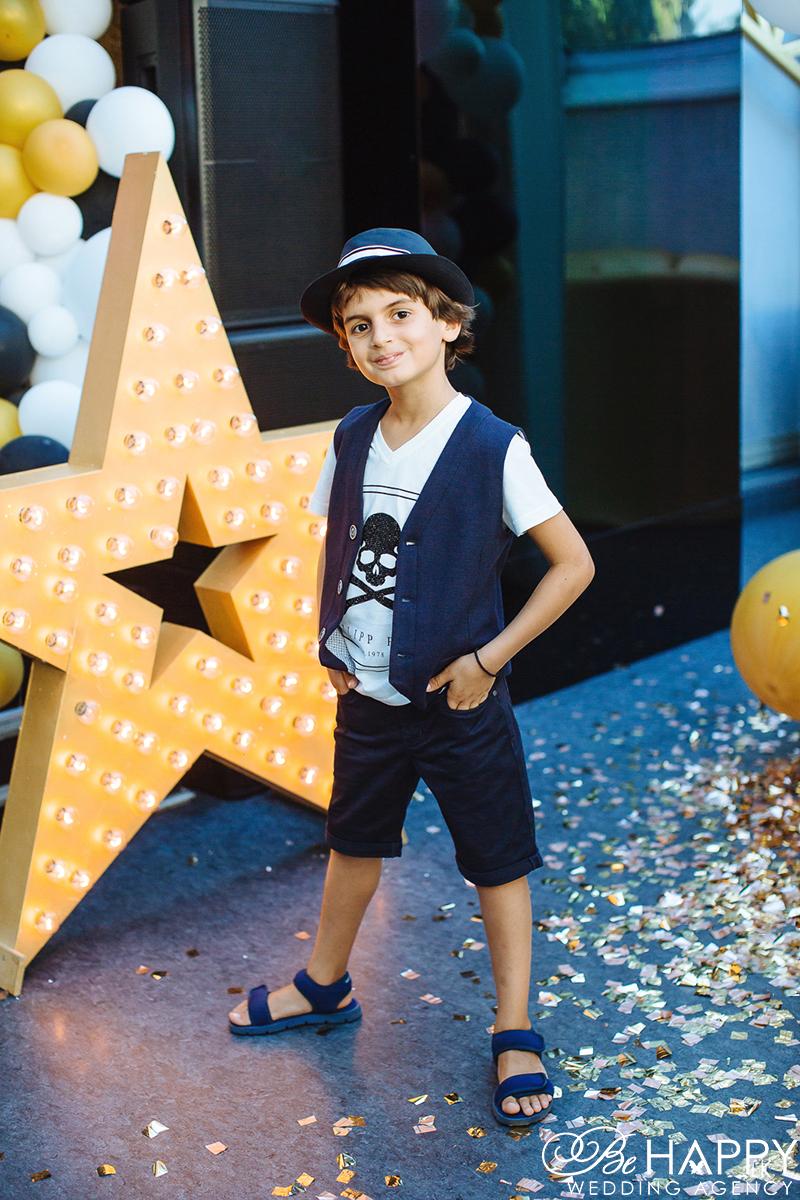Фото мальчика в шляпе возле декоративной звезды