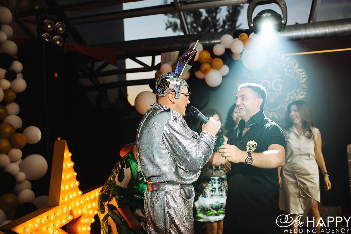 Верка Сердючка с микрофоном в руках танцует с гостем праздника